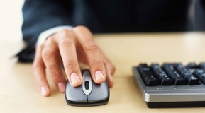 Picture of a man using the mouse and keyboard in an office setting.